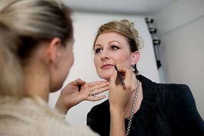 A woman having makeup applied by a professional makeup artist