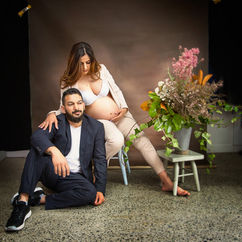 A couples photoshoot with pregnant woman in the studio with flowers by Angela Scott photographer