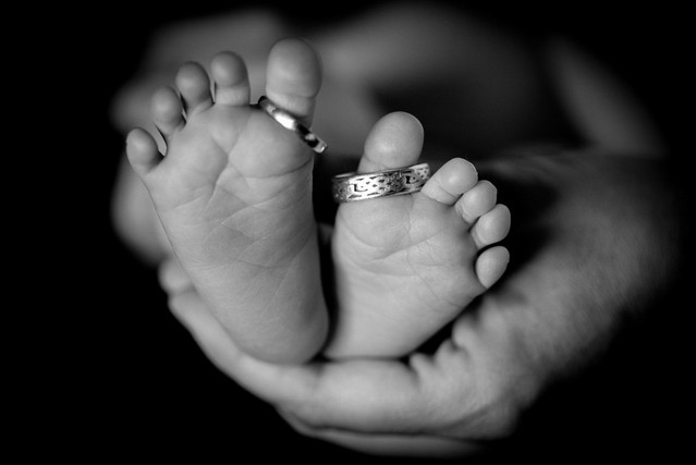 Baby feet and wedding rings with hands holding them