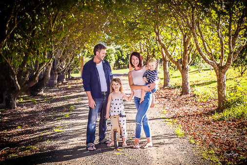 Lovely family photo on a country lane under the trees  with mum, dad and 2 kids.