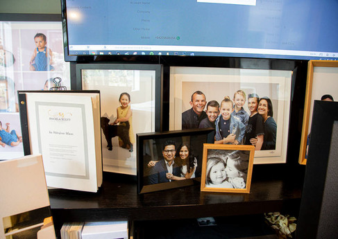 Interior of Auckland studio of Angela Scott Photography showing framed portrait examples