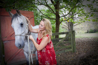 Photo of a lady in a red dress with her horse on a farm taken by Angela Scott photographer