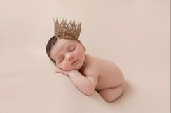 Newborn Boy in the studio asleep, wearing a crown
