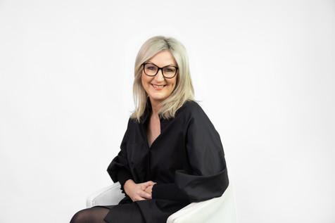 Professional studio business portrait of a lady sitting wearing a black jacket by Angela Scott photographer