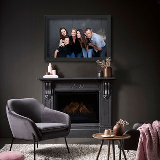 Framed family portrait on display above fireplace