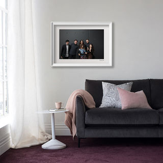 Lounge with a framed studio family portrait on the wall
