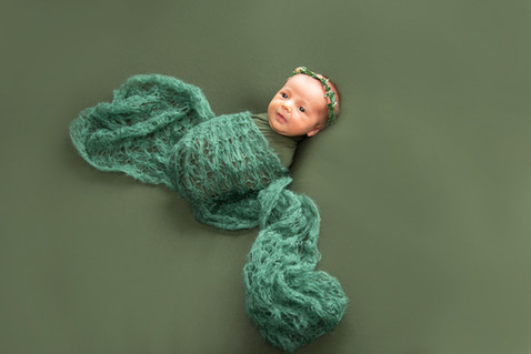 Newborn infant baby photoshoot wrapped in a green blanket