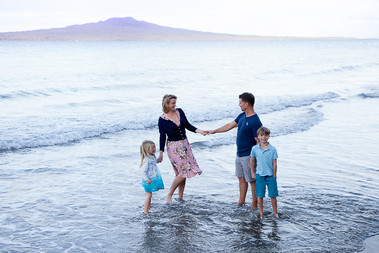 Family photo taken at the beach with Rangitoto island by Angela Scott photographer