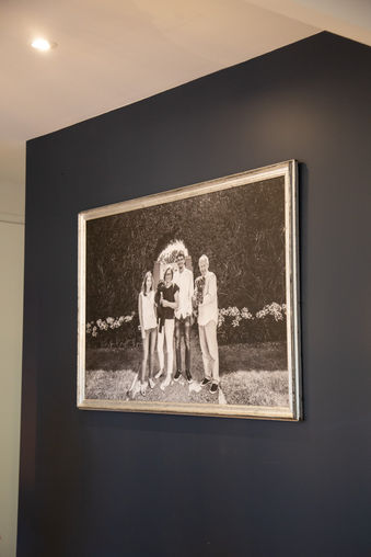 Black and white framed portrait shown hanging on a wall
