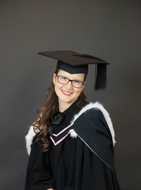 Woman smiling in graduation photoshoot in studio with cap and gown by professional photographer Angela Scott