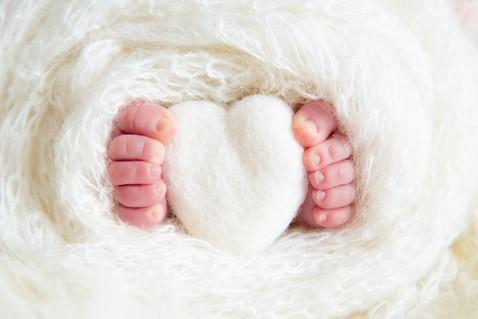 Cute newborn baby toes with love heart prop in studio photo shoot
