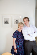 A couple pose with their framed family portraits hanging on the wall taken by Angela Scott photographer