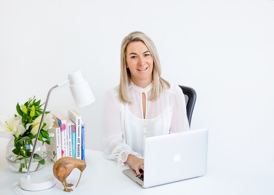 Professional commercial photography studio photo of woman in white shirt with laptop and office desk