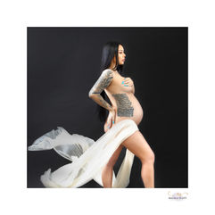 Profile studio photo of pregnant woman with tattoos by professional photographer Angela Scott