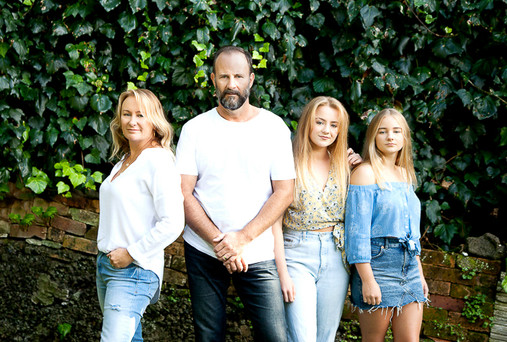 Location family photo with mum dad and 2 daughters with greenery background, photographed by Angela Scott