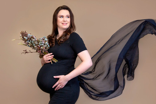 Pregnancy photoshoot in studio with lady in flowing black dress and flowers by Angela Scott photographer