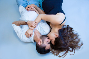 Man and pregnant lady kissing while lying on the studio floor during a professional photoshoot with Angela Scott photographer in Auckland