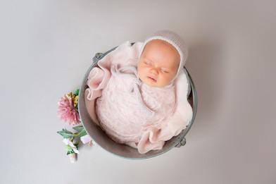 Newborn baby in a bowl asleep