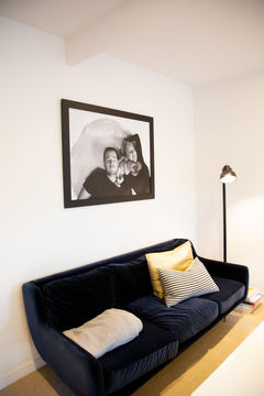 Photography wall art family portrait hanging above a lounge suite