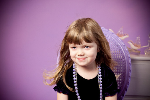 Child sitting on a chair with purple background in studio portrait by Angela Scott photographer