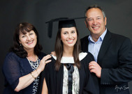 Professional studio graduation photo with a young woman graduate in her robe and cap with her parents