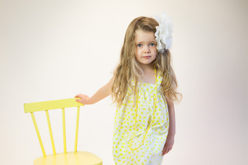 Professional children's portrait with yellow chair in the studio of professional photographer Angela Scott
