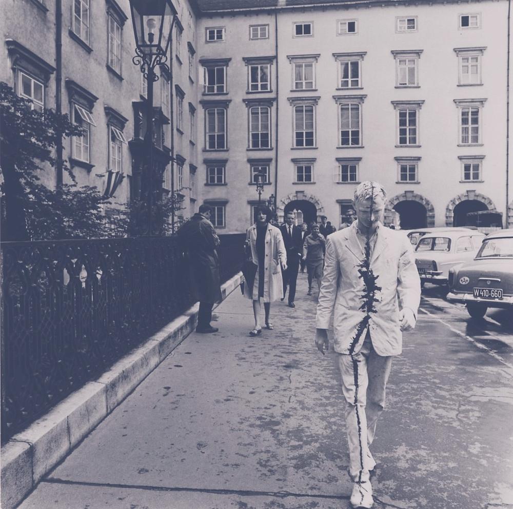 Günter Brus, Wiener Spaziergang, 1965, Performance in der Wiener Innenstadt. Günter Bruns, geboren 1938, lebt in Graz. ER zählt zu den Begründern des Winer Aktionismus. Seit Beginn der 1960er Jahre malt er Bilder, die zunehmend die Grenzen der Leinwand überwinden.