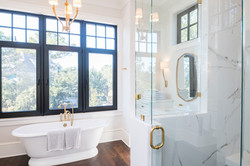Elegant master bathroom with tub and walk in shower accented in gold and black