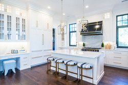 Large chef's kitchen with white cabinets and gold accents