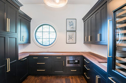 Walk-in butler's pantry with dark cabinets and gold accents in Kiawah Island home