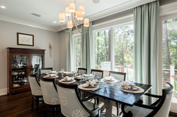 Dark wood pieces in the dining room with custom draperies by Aubergine Home Collection