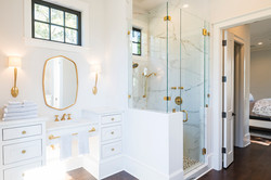 Gold accented master bath with towels and mirror by Aubergine Home Collection