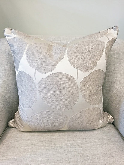Silver metallic throw pillow with repeating leaf pattern