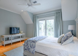 Modern beach house guest bedroom with custom furnishings by Aubergine Home Collection