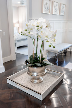 Faux orchid in a silver footed urn on foyer entryway table of elegant coastal home