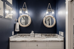 Nautical bathroom with dual-sink white vanity and navy blue walls