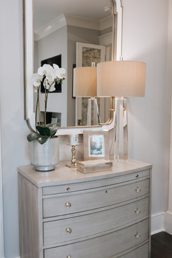 Accent decor pieces on a chest of drawers create an elegant vignette in front of a mirror
