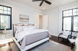 Downstairs master suite with bedding and furniture by Aubergine Home Collection