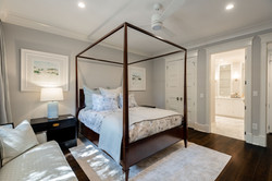 Guest bedroom with dark wood canopy bed for an elegant coastal style