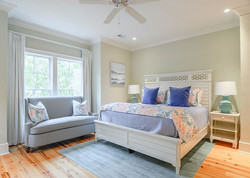Modern beach house guest room with custom coastal bedding by Aubergine Home Collection