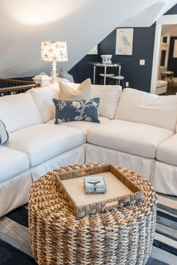 Slip-covered sectional sofa and decorative accent throw pillows and rattan ottoman by Aubergine Home