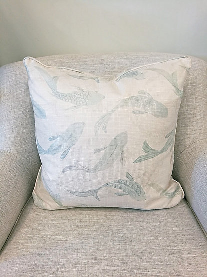Koi fish throw pillows in aqua with a linen background