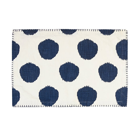 Woven cotton placemat with an indigo blue ikat-inspired polka dot pattern