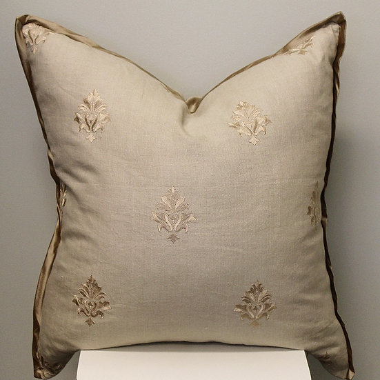Taupe embroidered throw pillow with a repeating medallion design