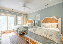Coastal double bed guest room with custom bedding and pillows by Aubergine Home Collection
