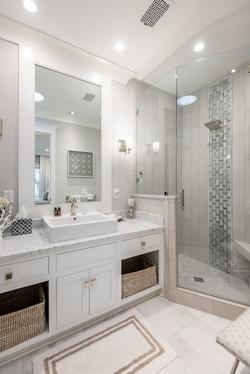 Elegant coastal guest bathroom with large vanity and custom glass-enclosed shower