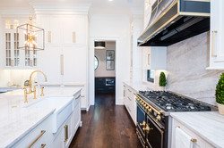 White kitchen with gold accents and walk-in butler's pantry
