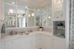 Elegant coastal master bedroom bathroom with custom tile and cabinetry