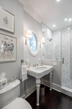 Elegant coastal bathroom with a custom tiled, glass-enclosure shower