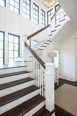 Main level staircase foyer with chest of drawers in corner